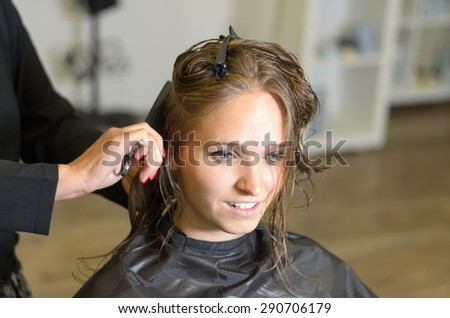 Close up Attractive Girl Inside a Salon, Smiling While a Hairdresser is Fixing her Hair. - stock photo