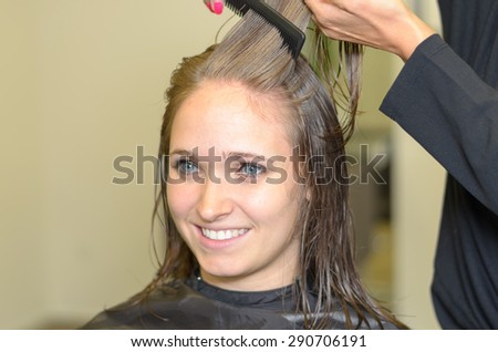 Close up Attractive Girl Inside a Salon, While a Hairdresser is Fixing her Hair. - stock photo