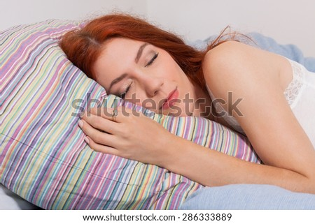 Close up Attractive Young Blond Woman Sleeping on her Bed Tightly While Lying on her Side Position. - stock photo