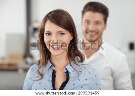 Close up Attractive Young Woman Inside the Office Smiling at the Camera In Front of her Handsome Partner.