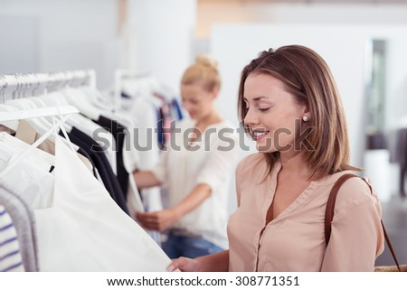 Close up Attractive Young Woman Looking at the Quality of a Shirt hanging on a Rail inside the Clothing Store. - stock photo