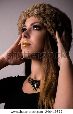 Close up Attractive Young Woman Wearing Furry Hat, Fashionable Necklace and Black Shirt, Looking Up with Both hands Touching the Head. Isolated on Light Brown Background. - stock photo