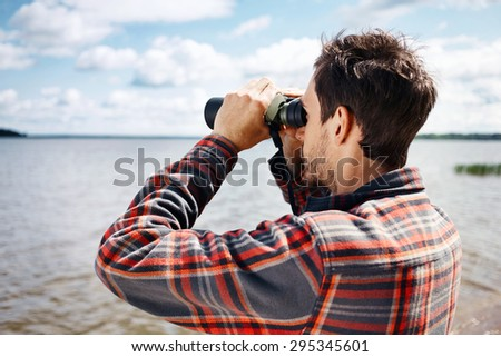 Close up back portrait man looks through binoculars while fishing at the lake on vacation - stock photo