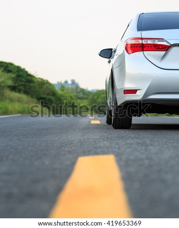 Close up back side of new silver car parking on the asphalt road - stock photo