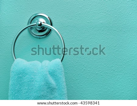 Close up background of a teal bathroom hand towel on a teal wall. - stock photo