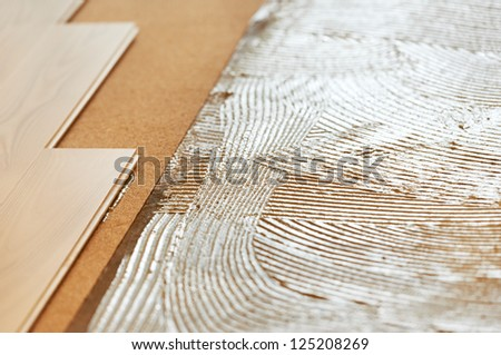 Close-up background of parquet with cork sublayer padding and glue on base during wood flooring - stock photo