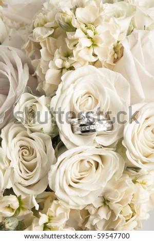 close-up background of white  bridal boquet with two rings - stock photo