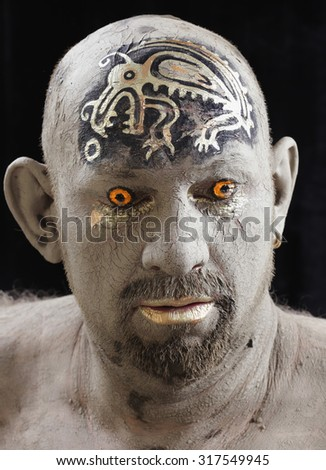 close-up bald man in a clay with ethnic pattern on the forehead on a black background Studio