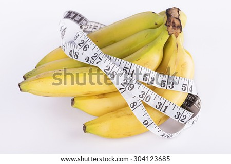 Close up Banana and measurement tape on white background - stock photo