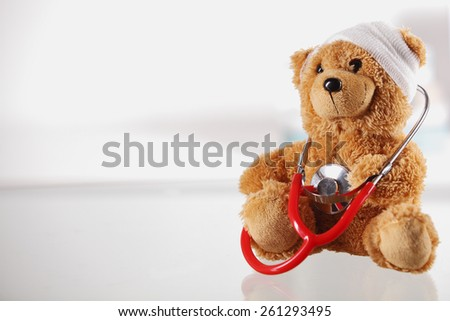 Close up Bandaged Teddy Bear on the Table Top with Stethoscope Device on White Background, Emphasizing Copy Space on the Left Side. - stock photo