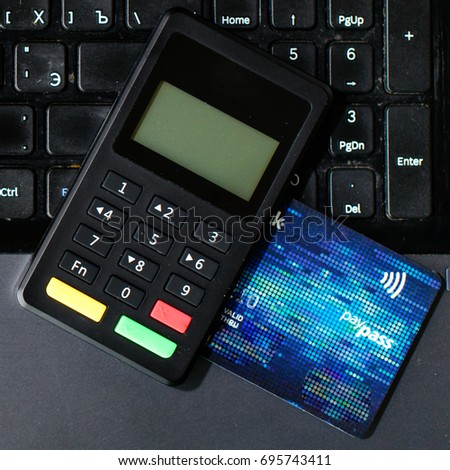 close-up bank card and payment device lying on keyboard, top view. Concept of internet crime, hacking, cyber crimes and virtual payments