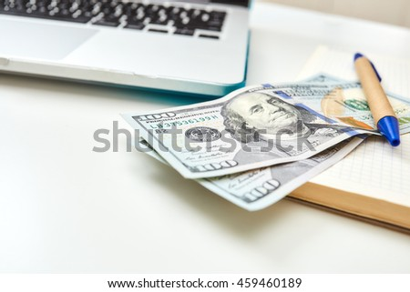 Close-up banknote on a notepad with a pen. Screen laptop computer. Freelance desktop with money and notepad.