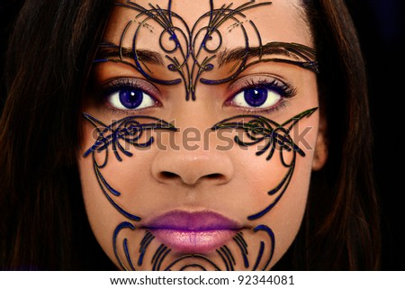 Close Up Beautiful Black Woman with Plastic Henna Art on Face and purple contact lenses. - stock photo