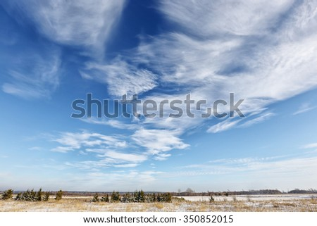 close-up beautiful cirrus clouds in the blue sky above snow-covered field on a sunny winter day - stock photo