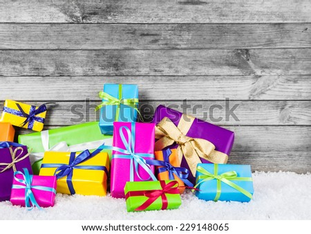 Close up Beautiful Colored Gift Boxes with Ribbon Laces For Christmas Festival Decorations. Captured with Gray Wooden Wall at the Background. - stock photo