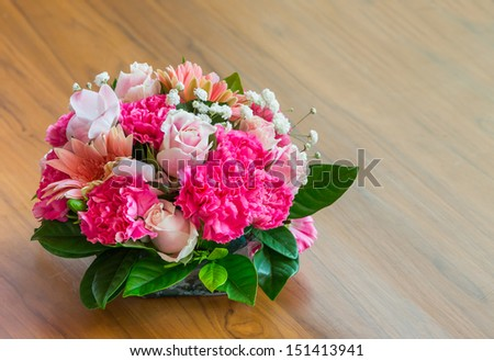 Close up beautiful flower bouquet on wooden table - stock photo