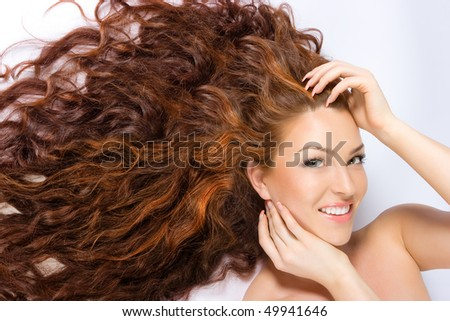 Close-up beautiful fresh bright woman with red (brown) long hair in studio shot - stock photo
