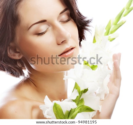 Close-up beautiful fresh face with gladiolus flowers in her hands - stock photo