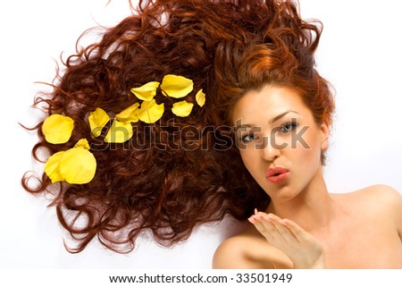 Close-up beautiful fresh red-haired lady with yellow petals in her hair blowing a kiss - stock photo