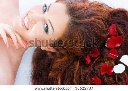 Close-up beautiful luxury fresh bright young lady lying in studio shot with rose petals in her red (brown) long hair - stock photo