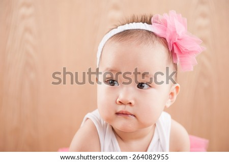 Close up beautiful 12 months old american baby girl in pink flower hat and tutu. - stock photo