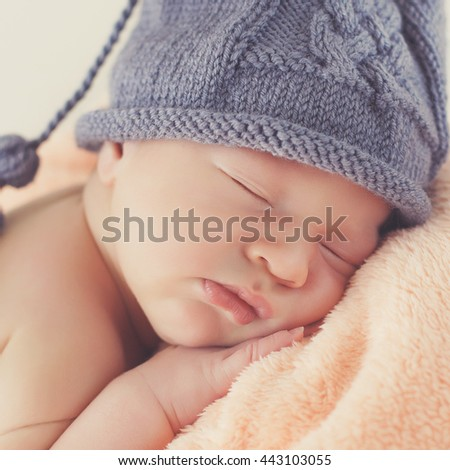 Close-up beautiful sleeping baby girl. Newborn baby girl, asleep on a blanket. A portrait of a beautiful, seven day old, newborn baby girl wearing a large, fabric rose headband. Closeup photo