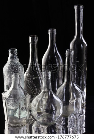 close-up beautiful transparent white empty bottles on the mirror surface on black background studio - stock photo