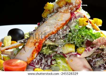 close-up beautifully designed caesar salad on a white plate on a black background studio - stock photo