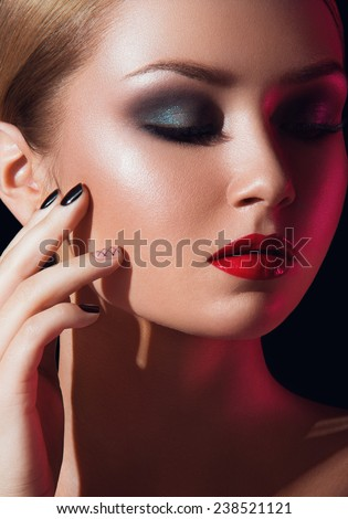 Close up beauty headshot of lady with green eyelids, red lipstick eyes closed, hand touching face on black background