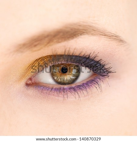 Close up beauty of a young woman eye wearing blue, purple and yellow make up eyeshadow, intensely looking at camera. - stock photo