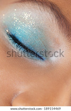 Close up beauty portrait detail of an african american black young woman closed eye wearing bright colorful blue eye make up and glitter for a fun party. Cosmetics, personal care and beauty lifestyle.