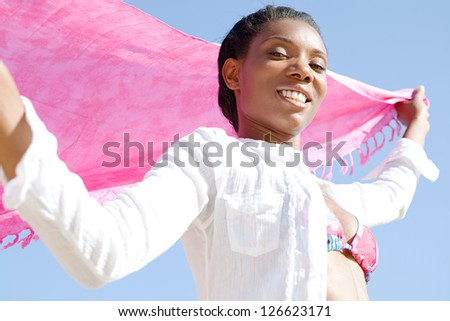 Close up beauty portrait of a black woman wearing a bright bikini and holding pink fabric in the air, smiling against a blue sky on the beach. - stock photo
