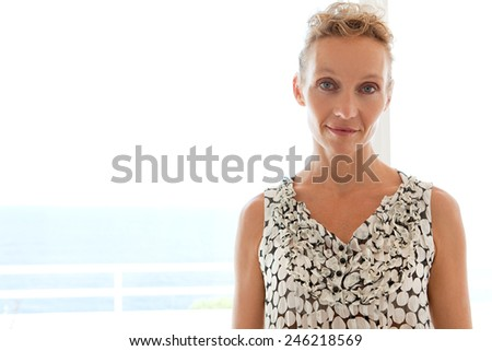 Close up beauty portrait of a healthy mature professional working woman smiling at the camera while standing against a bright window in a home office space, interior. Business and lifestyle at home. - stock photo