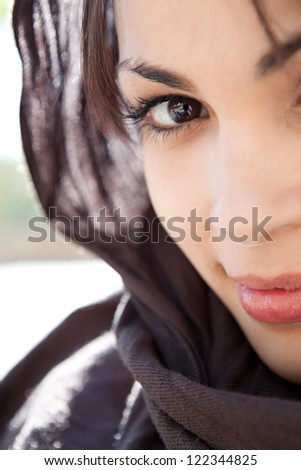 Close up beauty portrait of a muslim young woman wearing a head scarf and smiling at the camera, outdoors. - stock photo