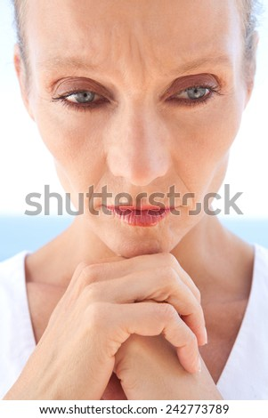 Close up beauty portrait of a senior mature healthy woman with blue eyes and flawless skin suffering and looking worried and emotional. Mature and aging face with a sad expression, outdoors.  - stock photo