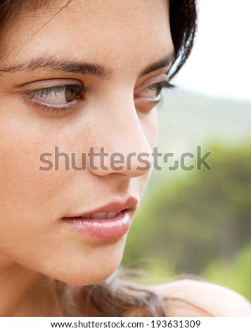 Close up beauty portrait of a thoughtful exotic young woman relaxing in nature, thoughtfully looking away and enjoying a summer holiday and being serene outdoors. Health and beauty lifestyle.