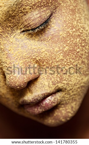 Close up beauty portrait of a young african american black girl half face with yellow cosmetic powder covering her face, with her eyes closed. - stock photo