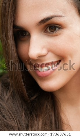 Close up beauty portrait of a young and attractive elegant latino woman with perfect healthy skin and dark long hair smiling. Beauty and wellness lifestyle outdoors.