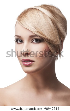 close up beauty portrait of a young and cute blond girl with hair style over white. her face is turned three-quarters, she looks in to the lens and smiles