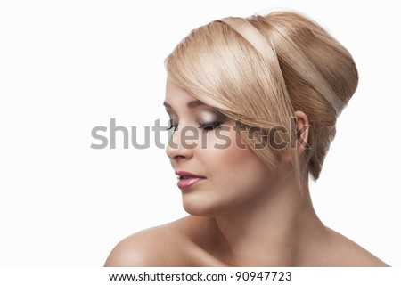 close up beauty portrait of a young and cute blond girl with hair style over white. she's almost turned in profile, looks down and slightly smiles. - stock photo