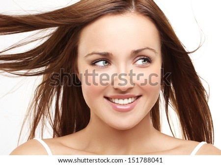 Close-up, beauty portrait of a young brunette woman with beautiful smile and fluttering hair - stock photo