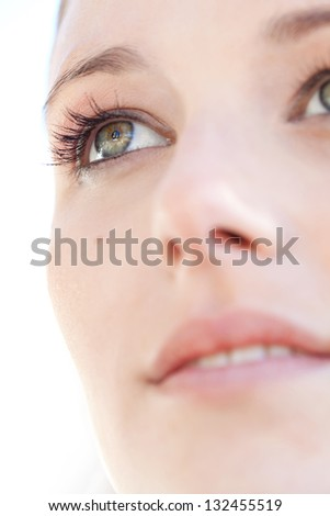 Close up beauty portrait of a young caucasian healthy woman face and eye looking up with long eyelashes. - stock photo