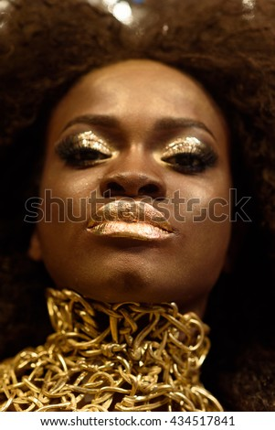 Close up beauty portrait of a young female fashion model with curly hair and gold makeup - stock photo