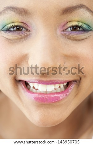 Close up beauty portrait of a young girl face with voluptuous lips wearing a rainbow color eye shadow and smiling with glossy pink lipstick. Perfect skin.