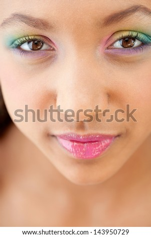Close up beauty portrait of a young girl face with voluptuous lips wearing a rainbow color eye shadow and smiling with glossy pink lipstick.