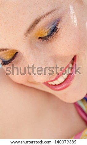 Close up beauty portrait of a young woman wearing fresh colorful make up , eyeshadow and lipstick during a spring day, smiling with her eyes shut. - stock photo