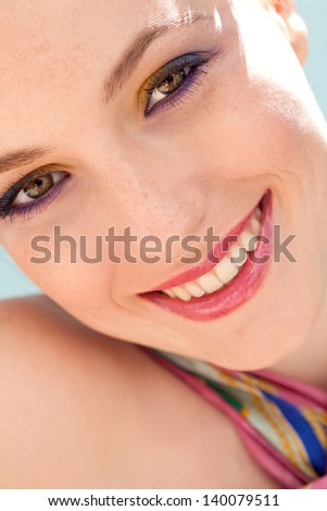 Close up beauty portrait of a young woman wearing fresh colorful make up , eyeshadow and lipstick during a sunny spring day, smiling at the camera.