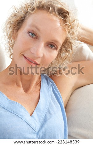 Close up beauty portrait of an attractive middle aged healthy woman relaxing on a white sofa at home, looking at the camera smiling. Interior home living and lifestyle. - stock photo