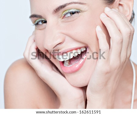 Close up beauty portrait of an attractive woman wearing fantasy colorful make up for a party, joyfully smiling with a fun and excited expression, indoors.
