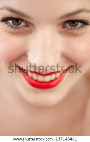 Close up beauty portrait of an attractive young woman and wearing red lipstick cosmetics on her lips, and beautiful eye lashes, smiling.